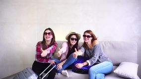 Pretty girls going on trip and preparing suitcases on couch in afternoon room. Pretty female friends together collect large gray and blue suitcases, add up all stock video