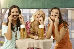 Pretty girls having fun and beer. Pretty girls having fun, forming moustache from hair, drinking beer in outdoor bar, smiling Stock Image
