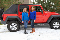 Pretty girls having fun by a Jeep. Pretty girls posing in front of a red Jeep in the snow Royalty Free Stock Photos