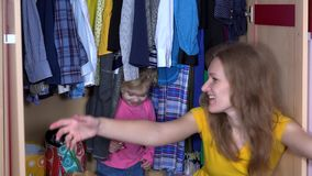 Pretty girls hiding in clothes closet. Mother and daughter open closet and smile stock footage