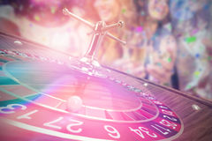 Pretty girls holding wine glass against 3D image of ball on wooden roulette wheel Stock Photo