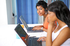 Pretty girls on laptops. Two pretty girls working on laptops, horizontal image with selective focus Royalty Free Stock Images