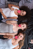 Pretty girls lying on the bed and eating lollipops Royalty Free Stock Photo