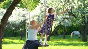 Pretty girls mother and daughter have fun on wooden swing. Static shot stock footage