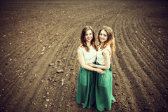 Pretty girls outdoor walking and embrancing in the field Royalty Free Stock Photography