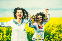 Pretty girls outdoor walking in the field in embroidery shirts Royalty Free Stock Photos