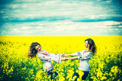 Pretty girls outdoor walking in the field in embroidery shirts Royalty Free Stock Images