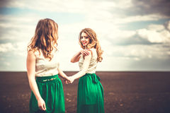 Pretty girls outdoor walking in the field, holding hands Royalty Free Stock Photography