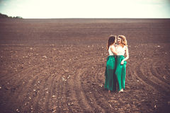 Pretty girls outdoor walking in the field, holding hands Stock Images