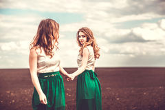 Pretty girls outdoor walking in the field, holding hands Royalty Free Stock Photos