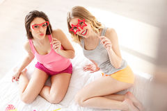 Pretty girls playing with artificial glasses. Joyful young women having fin at home. They are wearing paper eyeglasses and posing. Friends are sitting on bed and stock photography