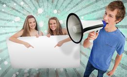 Pretty girls pointing to copy space with young man shouting thro Royalty Free Stock Photo