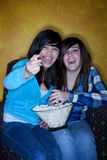Pretty girls with popcorn watching television Stock Photos