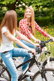 Pretty girls posing with bikes in park. Two young beautiful girls with long hair looking at each other smiling while riding their mountain bikes in a green park Stock Photo