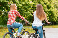 Pretty girls posing with bikes in park. Two young beautiful girls with long hair looking at each other smiling while riding their mountain bikes in a green park Royalty Free Stock Image