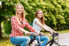 Pretty girls posing with bikes in park. Two young beautiful girls with long hair smiling while riding their mountain bikes in a green park ,selective focus Royalty Free Stock Image