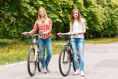 Pretty girls posing with bikes in park. Two young beautiful girls with long hair standing in a green park holding their bikes and smiling, wearing casual clothes Royalty Free Stock Images