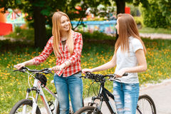 Pretty girls posing with bikes in park. Two young beautiful girls with long hair walking with their bikes looking at each other and smiling in a green park Stock Image