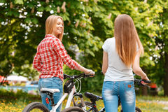 Pretty girls posing with bikes in park. Two young beautiful girls with long hair walking with their bikes looking at each other and smiling in a green park, view Stock Photo
