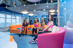 Pretty girls posing in recreational area of gym Royalty Free Stock Photos