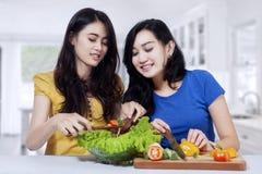 Pretty girls preparing vegetables salad Stock Photo