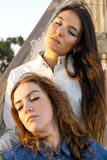 Pretty Girls Relaxing on Wooden Stairs Royalty Free Stock Photos