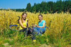 Pretty girls rest from riding bike Stock Photos
