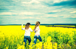 Pretty girls running  in the field in embroidery shirts Royalty Free Stock Images