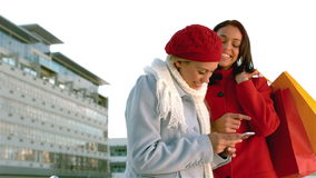 Pretty girls with shopping bags laughing looking at a smartphone. In slow motion stock footage