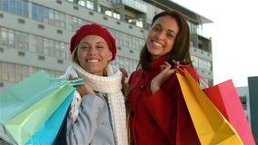Pretty girls with shopping bags smiling at the camera. In solw motion stock video footage