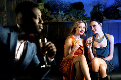 Pretty girls staring at handsome young man. Attractive young girls staring at handsome young men in night club Royalty Free Stock Photo