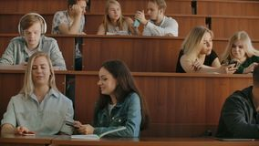 Pretty girls students are using smartphone, watching screen, talking and laughing sitting at desks at university. Social stock footage
