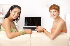 Pretty girls talking on sofa smiling Stock Photo