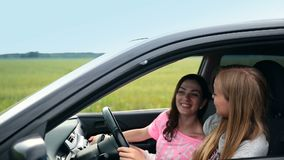 Pretty girls traveling countryside by car stock footage