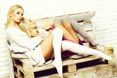 Girls in sweaters and socks. Pretty girls or two cute women with blond hair in home sweaters and socks sit on wooden pallet sofa on white brick wall stock images