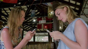 Pretty girls using smartphones in asian bar. Professional shot in 4K resolution. 074. You can use it e.g. in your commercial video, travel, presentation stock video footage
