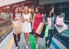 Pretty girls are walking together in mall. They are shopping. Young women have bags in their hands. Girls are laughing. And having fun stock photography