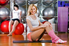 Pretty girls warming up in fitness center Stock Photos