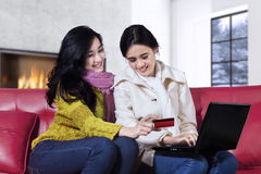 Pretty girls with winter clothes shopping online Stock Photography