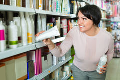 Pretty glad charming woman choosing hair care products. In shop and smiling stock images