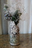 Pretty glass vase filled with silver beads,snowflakes and pine branches Royalty Free Stock Images