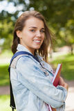 Pretty gleeful student holding folder and notebook Stock Photography