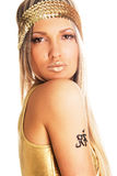 Pretty golden girl with tattoo. Pretty girl in golden clothing with tattoo on a shoulder Stock Photography