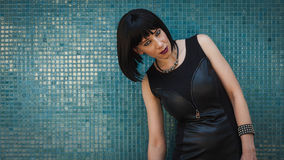 Pretty goth girl posing against a blue wall Royalty Free Stock Images