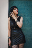 Pretty goth girl posing against a blue wall Royalty Free Stock Image
