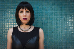 Pretty goth girl posing against a blue wall Royalty Free Stock Photo