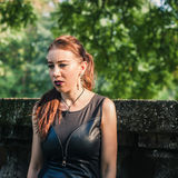 Pretty goth girl posing in a city park Stock Image