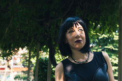 Pretty goth girl posing in a city park Stock Photo