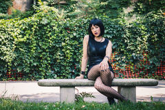 Pretty goth girl sitting in a city park Royalty Free Stock Photos