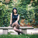 Pretty goth girl sitting in a city park Royalty Free Stock Image